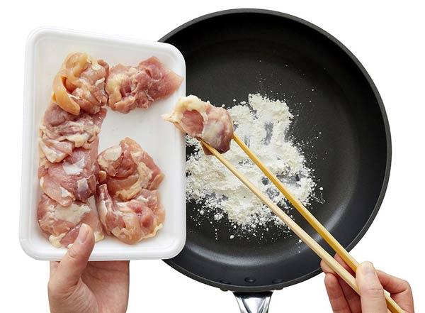 フライパンの中で鶏肉に粉をまぶす