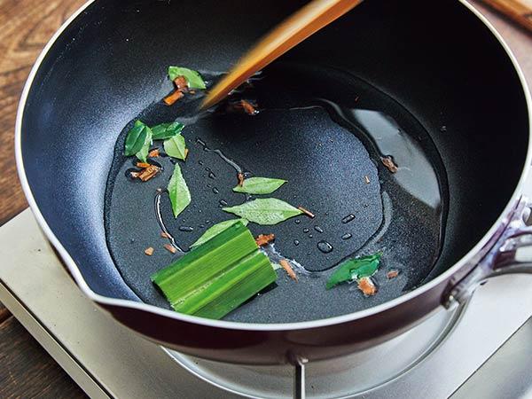 フライパンにココナッツオイルを熱し、カレーリーフとパンダンリーフ、シナモンを炒める