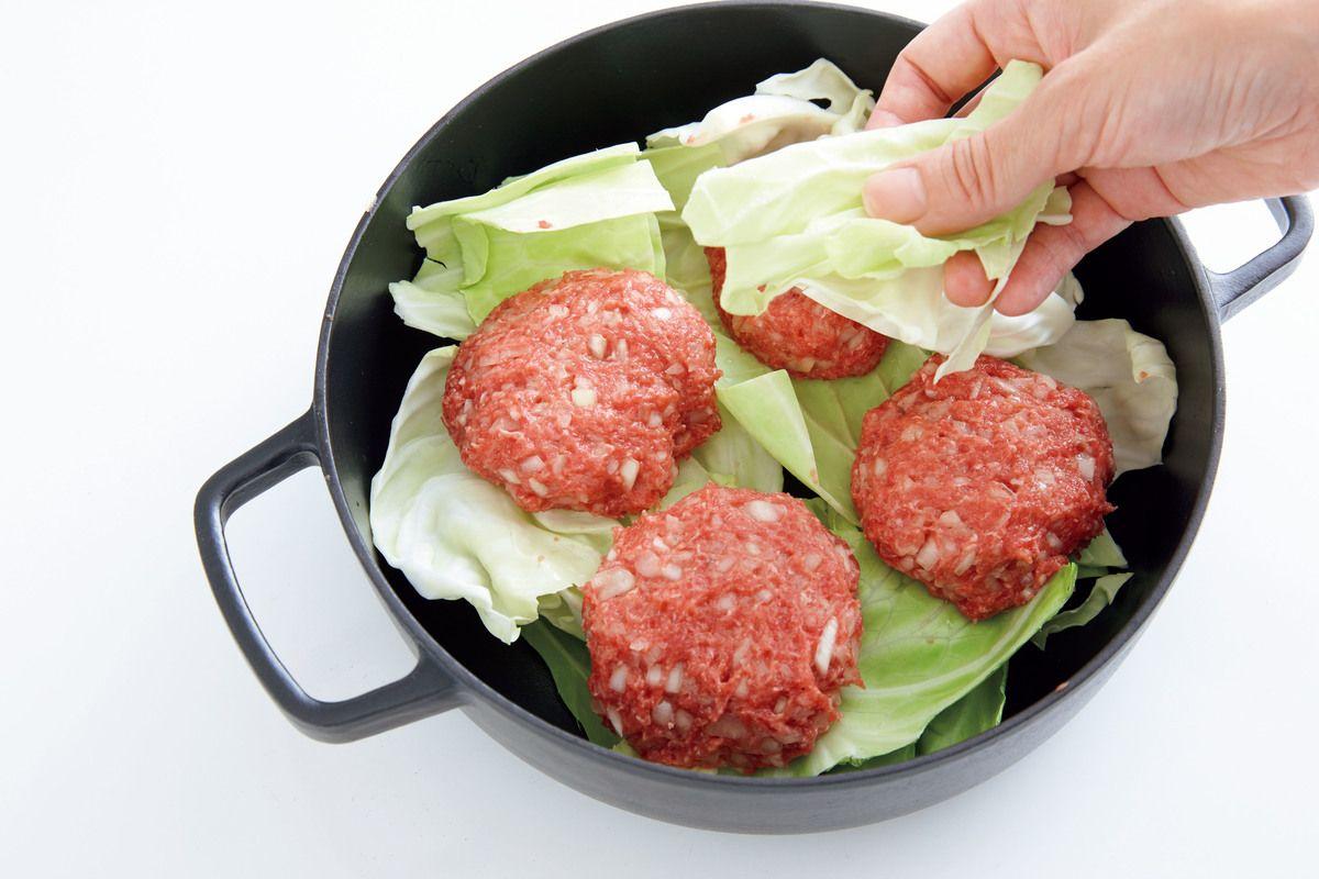肉だねとキャベツを重ねて蒸し煮にする。