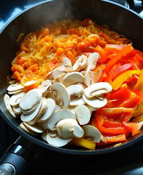 炒めたたまねぎとトマトにベーコン、パプリカ、マッシュルームを加える